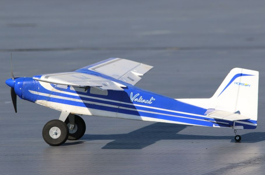 a light blue RC airplane sitting on the ground