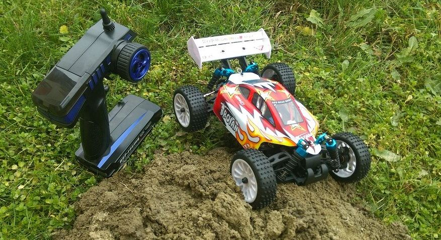 an RC toy car and its black controller on the ground