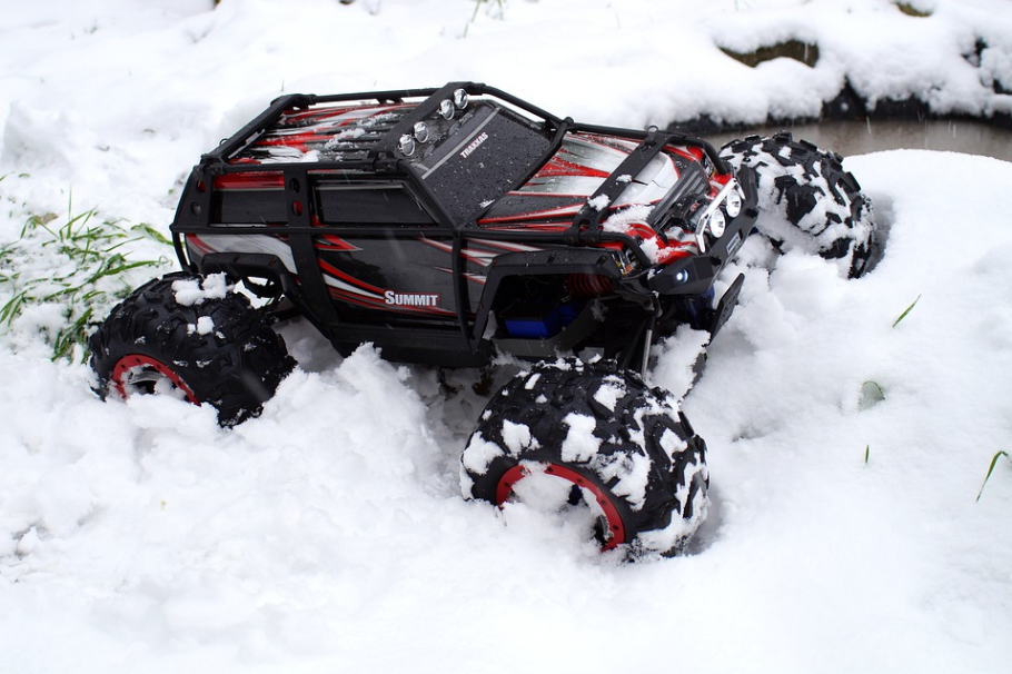 black-and-red RC toy car tearing through the snow
